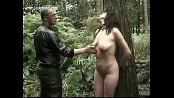 milf slave tied to a tree gets spanked.