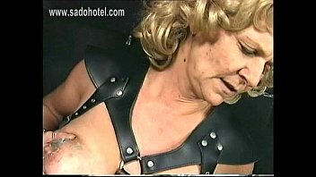 hot older slave with big tits wearing leather.