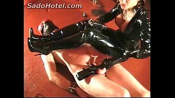 latex wearing mistress stands on and electrocutes cock.