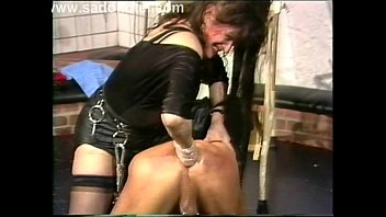 mistress wearing leather puts some lube on slave.