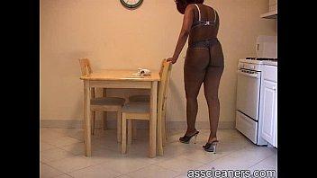 chubby ebony mistress in bikini cleans the table.