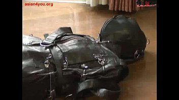 ballgagged asian girl tied into a leather sleepsack.