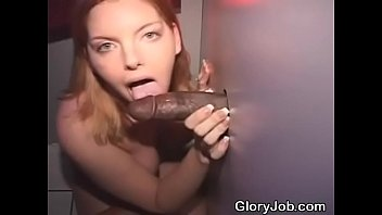 redheaded beauty taking interracial facial through a glory hole