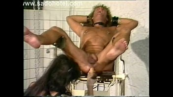 mistress wearing leather puts dildo in the ass.