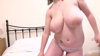 dd brunette flashses her massive tits in the bedroom