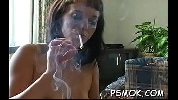 busty bombshell enjoying a gulp and a smoke.